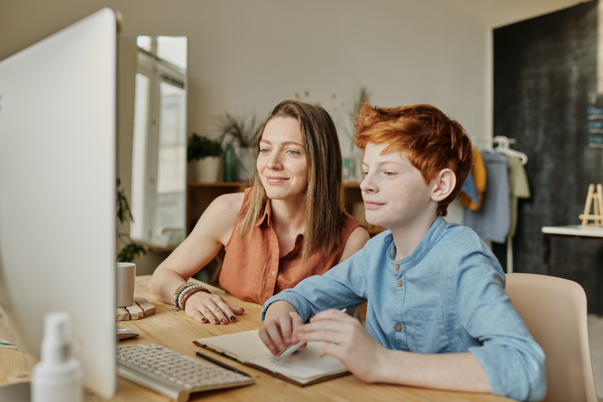 photo-of-woman-and-boy-smiling-while-watching-through-imac-4145350